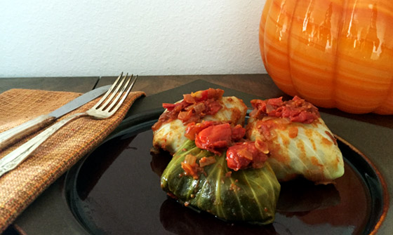 Vegan stuffed cabbage rolls on fall color plate with glass pumpkin in ...