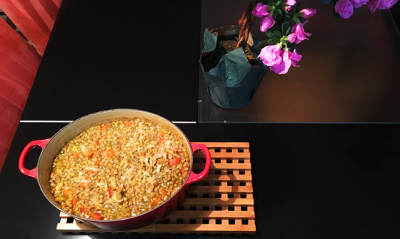 Soup in pot on table with flower centerpiece
